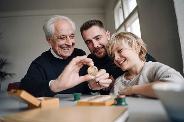 Three generations playing marbles